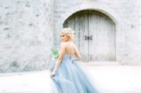 a strapless icy blue wedding ballgown with a layered skirt with a train is a fit for an ice queen