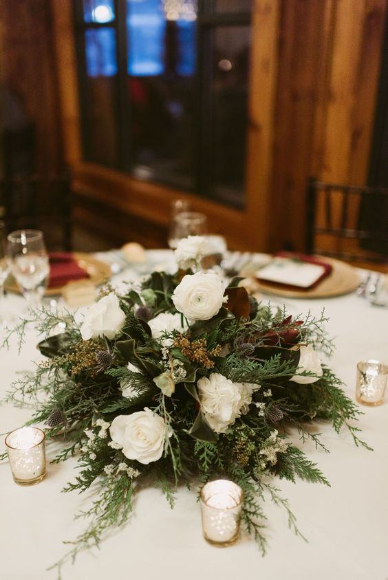 a stylish and non typical Christmas wedding centerpiece of greenery ferns, white blooms and magnolia leaves is pure beauty