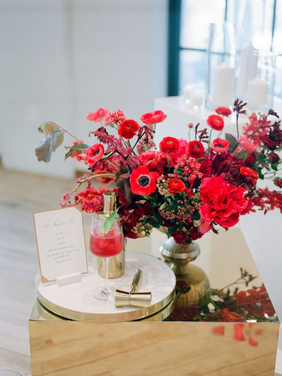 a super bold Christmas wedding centerpiece of a gold bowl, red, fuchsia and burgundy blooms and some foliage is amazing