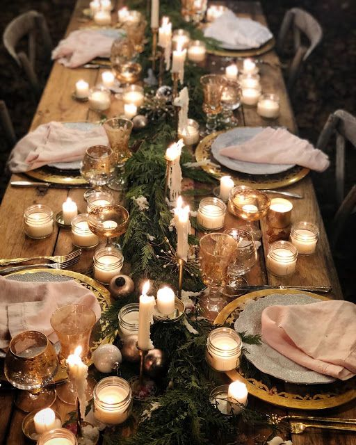 a super cozy and welcoming Christmas tablescape with an evergreen runner, lots of candles, vintage glasses and gold chargers