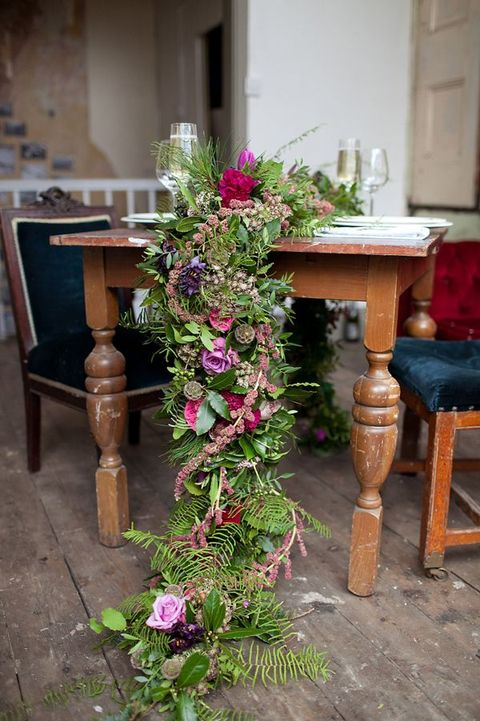 a super textural and lush greenery and fern garland with bright blooms in pink, purple and fuchsia for a bright jewel tone wedding