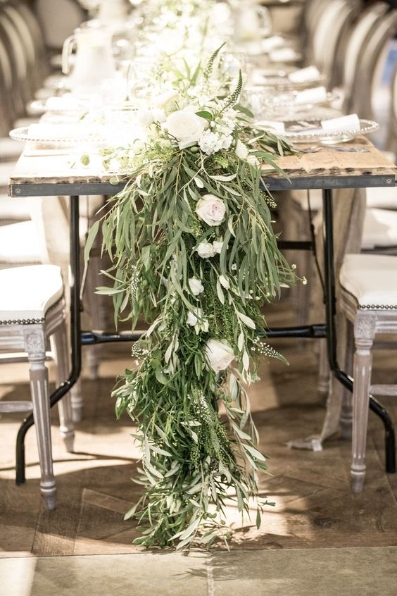 a textural greenery wedding table garland with white blooms is a lush and wild decoration