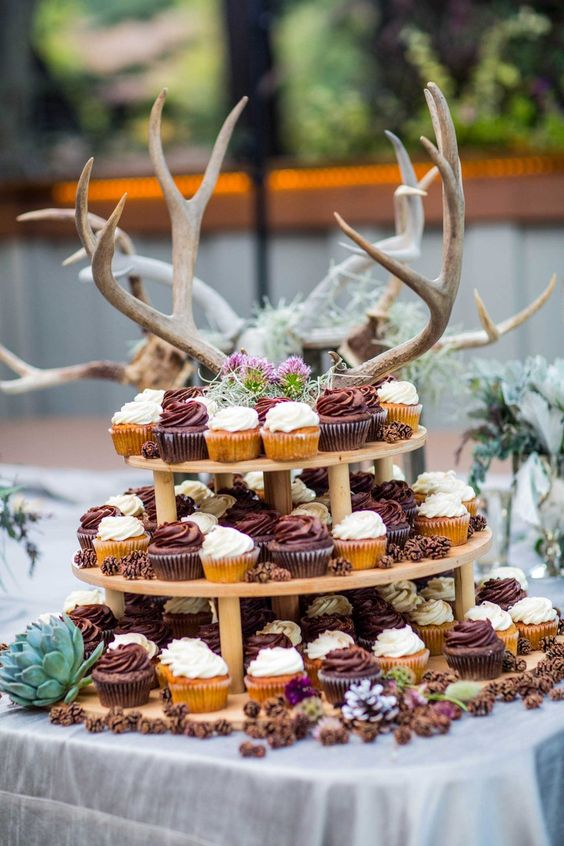 a tiered wedding dessert stand with blooms, greenery, antlers and lots of cupcakes is perfect for any woodland wedding