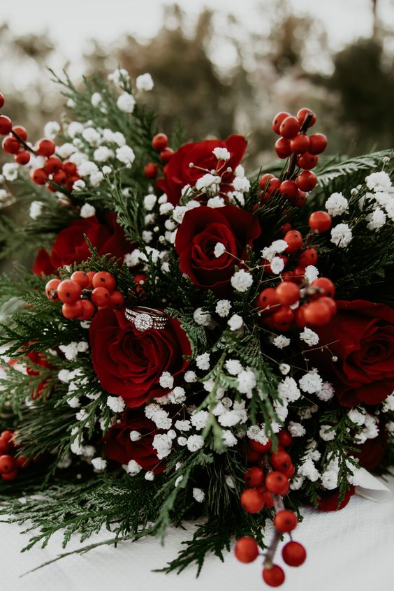 a traditional Christmas wedding bouquet of red roses, berries, greenery and baby's breath is contrasting