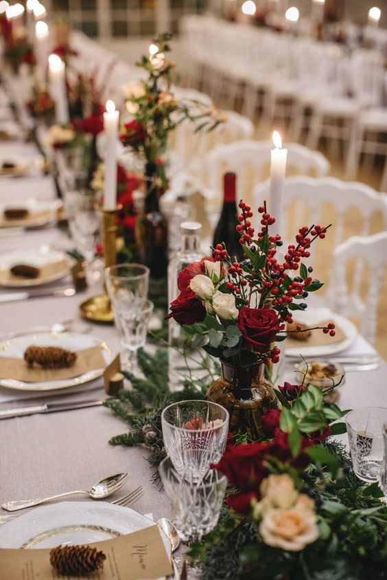 a traditional and chic Christmas tablescape with evergreens, greenery, white and red roses and berries, pinecones and tall and thin candles