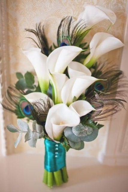 a unique wedding bouquet with white callas,peacock feathers and pale eucalyptus plus a turquoise wrap
