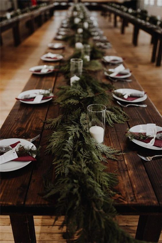 a very simple rustic tablescape with an uncovered table, a fern runner and evergreens, burgundy napkins