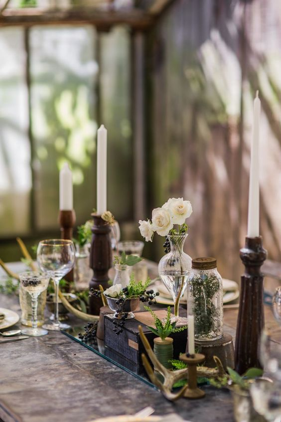 a vintage botanical wedding centerpiece of greenery, white blooms and berries in vases and jars and tall and thin candles