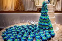 a wedding backdrop with a sugar peacock on top and matching cupcakes that form its tail