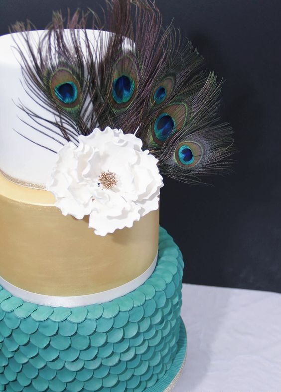 a wedding cake in gold, blue, white, with a sugar bloom and peacock feathers for decor