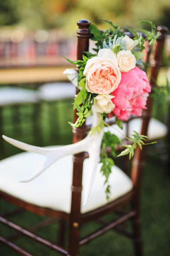 a wedding chair decorated with antlers, greenery, peachy and bright pink blooms is a bold and chic idea