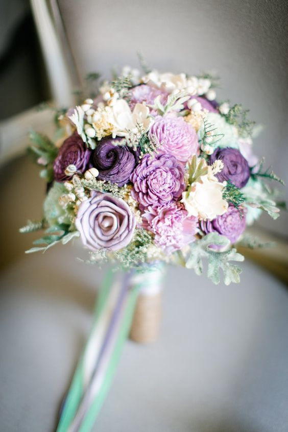 a whimsy purple, lavender and mint-colored wedding bouquet with lots of blooms and greenery
