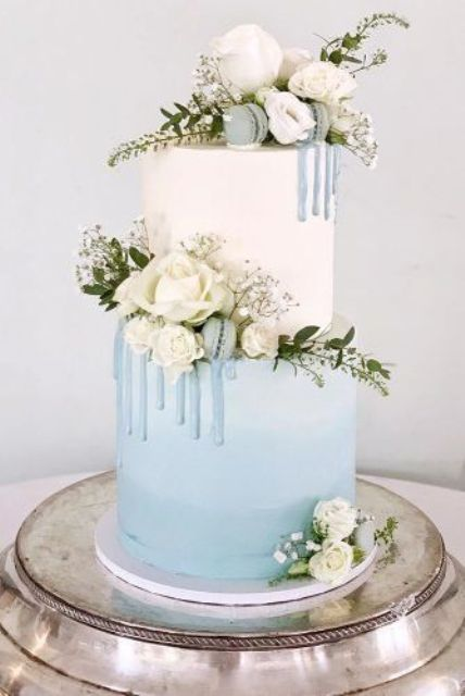a white and ice blue winter wedding cake with baby's breath, white blooms and blue macarons