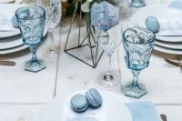a white and ice blue winter wedding tablescape with blue napkins, glasses and macarons plus gold cutlery is chic