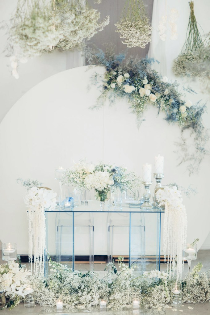 a white backdrop decorated with white and ice blue blooms and an ice blue sheer glass table and blooms for an ethereal look