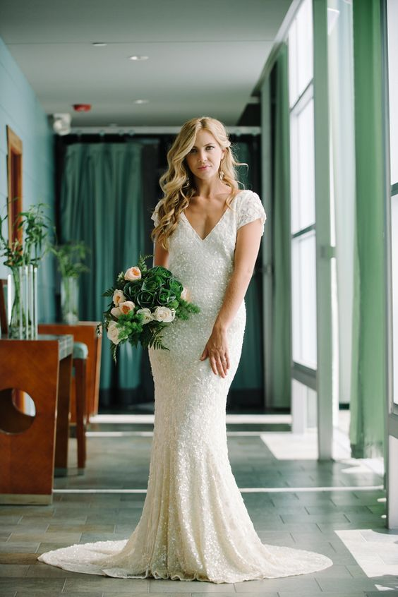 a white sequin V cut wedding dress with short sleeves and a small train is a chic and timeless idea