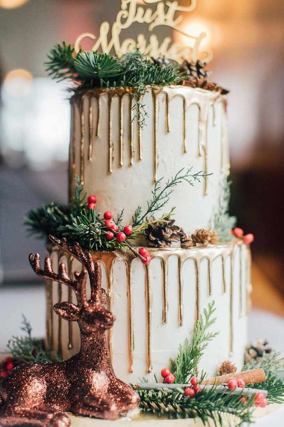 a white wedding cake with gold drip, fir twigs, pinecones, a glitter deer and cinnamon sticks is a very Christmassy piece