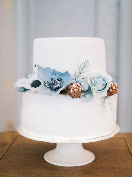 a white wedding cake with ice blue sugar blooms and pinecones is a great idea for a winter wedding