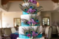 a white wedding cake with turquoise ribbons, peacock feathers and purple orchids for decor
