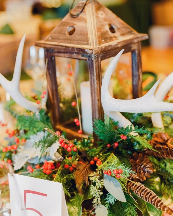 a winter wedding centerpiece of greenery, berries, pinecones, feathers, antlers and a candle lantern in the center