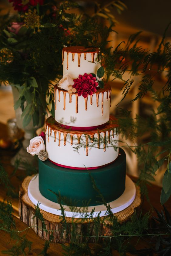 a woodland Christmas wedding cake in white, hunter green and orange, with drip and fresh blooms looks very unusual and modern