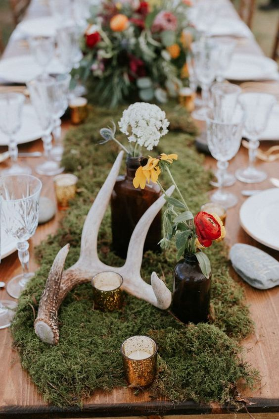 a woodland wedding table with a moss runner, candles, bright blooms in apothecary bottles and antlers is very chic