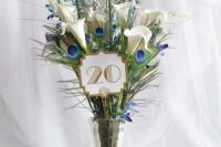 an art deco wedding centerpiece with peacock feathers and white callas plus a table number