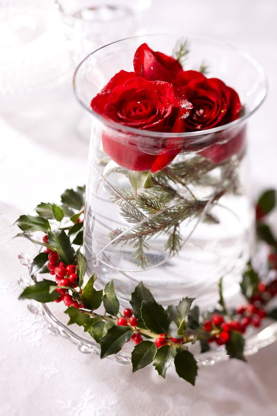 an easy Christmas wedding centerpiece of fir branches, red roses and a berry wreath wrapping the vase