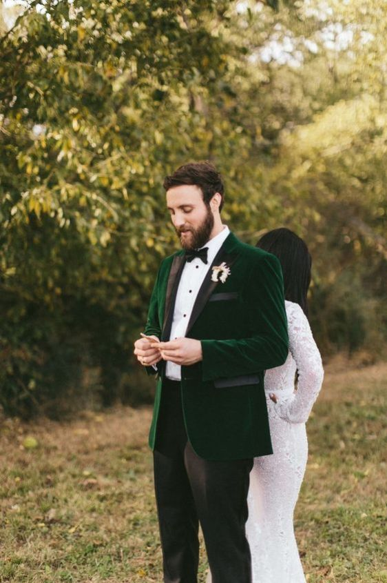 an emerald velvet tux with black lapels, a white button down, a black bow tie, black pants