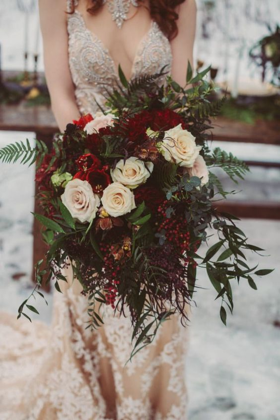 an exquisite Christmas wedding bouquet of white, burgundy blooms, berries and lots of greenery