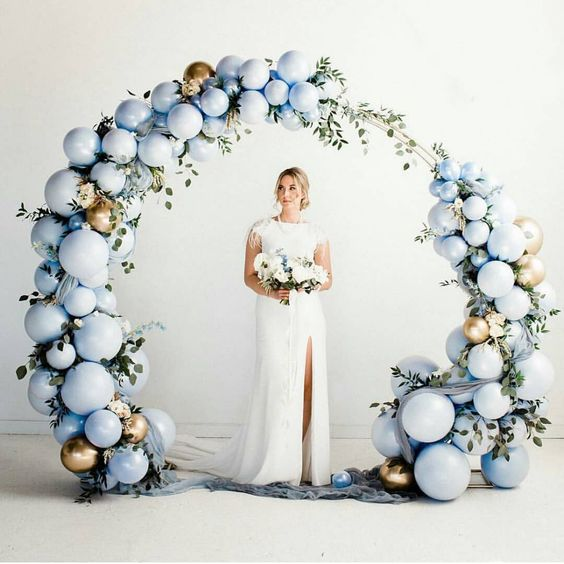 an ice blue and gold balloon plus greenery round wedding arch is a beautiful idea for a modern winter wedding