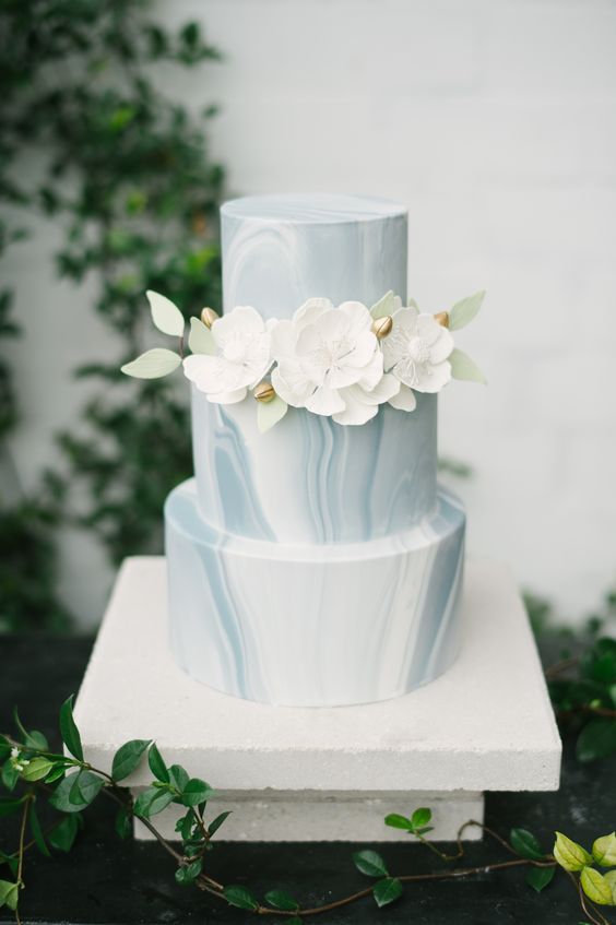 an ice blue marble winter wedding cake with white sugar blooms is a refined and chic idea