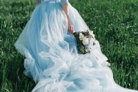 an ice blue wedding dress with a fully embellished bodice with long sleeves and a tiered skirt with a long train