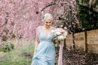 an ice blue wedding dress with a sheer beaded coverup and a deep neckline plus a matching floral headpiece