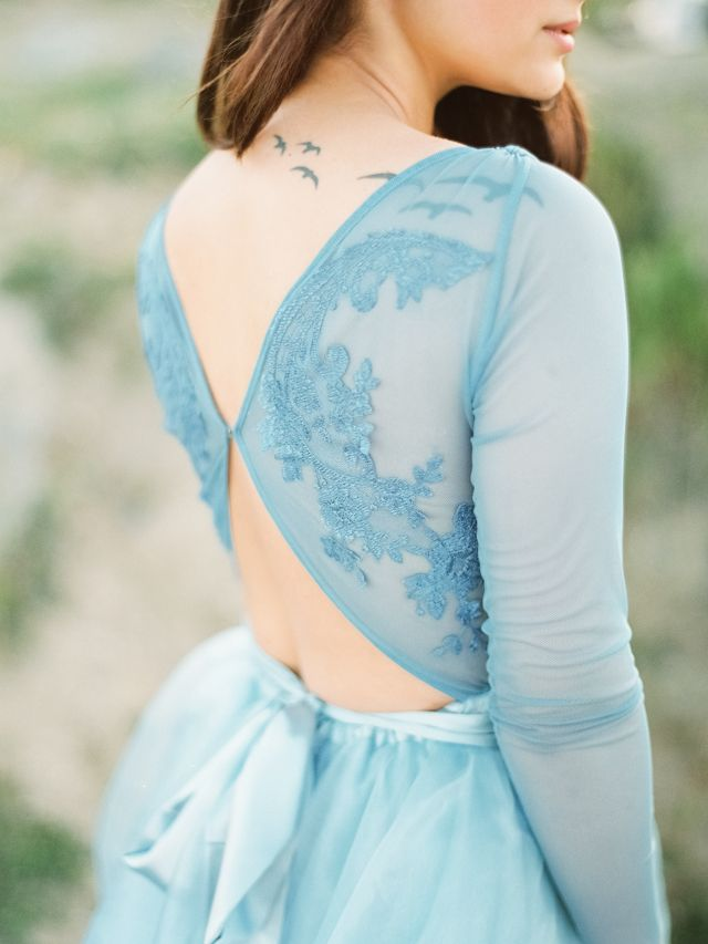 an ice blue wedding dress with an illusion lace top with back cutouts and a flowy skirt for a winter bridal look