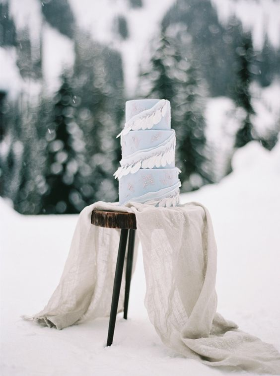 an ice blue winter wedding cake decorated with white feathers is a lovely and bold idea to go for