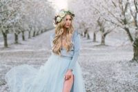 an ice blue winter wedding dress with a shiny long sleeve bodice and a layered skirt with a side slit plus a statement necklace