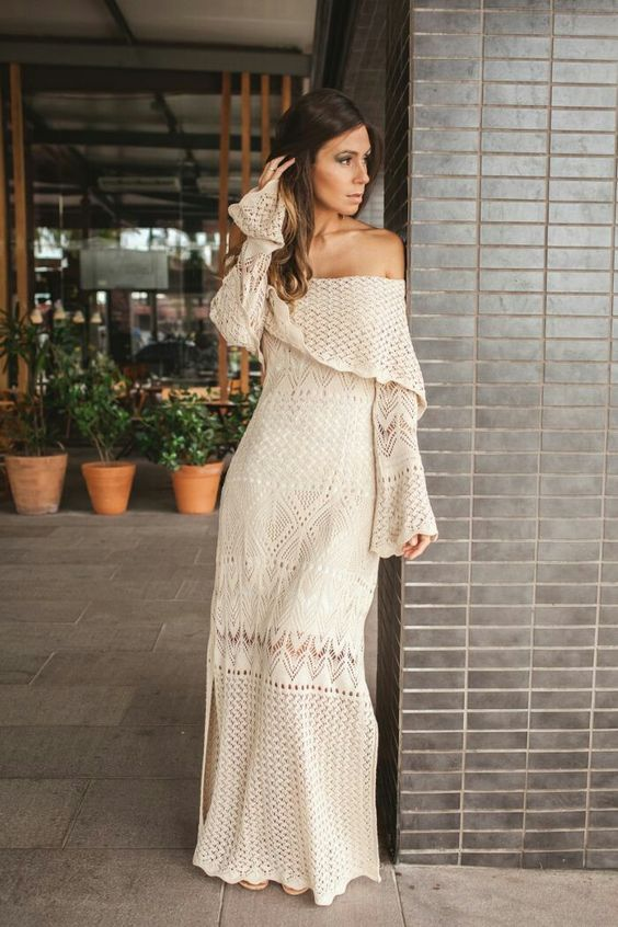 an incredibly romantic off the shoulder crochet maxi wedding dress with a slit, bell sleeves and a tiered neckline for a boho bride