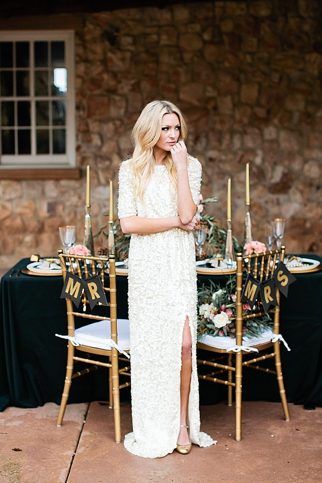 an ultra-modern wedding gown with long sleeves, a slit and with white sequins all over the dress