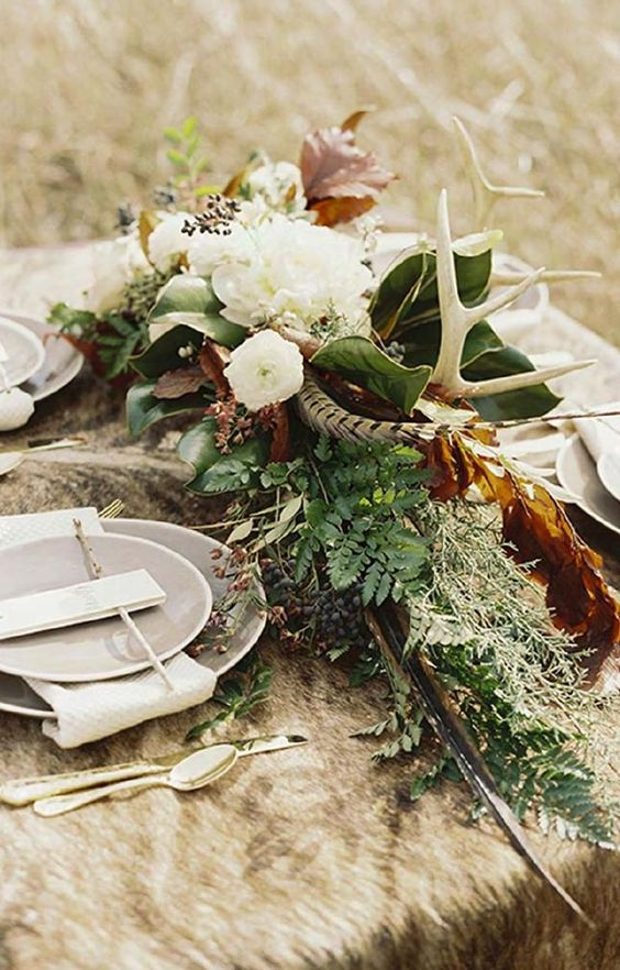 wedding table decor done with greenery, dried leaves, white blooms, privet berries and antlers plus faux fur on the table