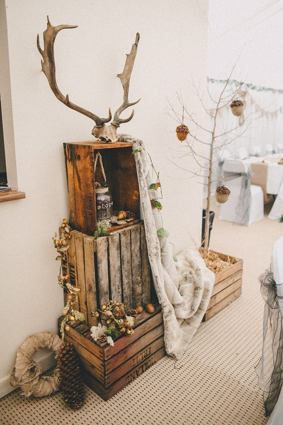 woodland wedding decor of crates, pinecones, cotton, dried leaves, a blanket and antlers on top will fit a fall or winter wedding