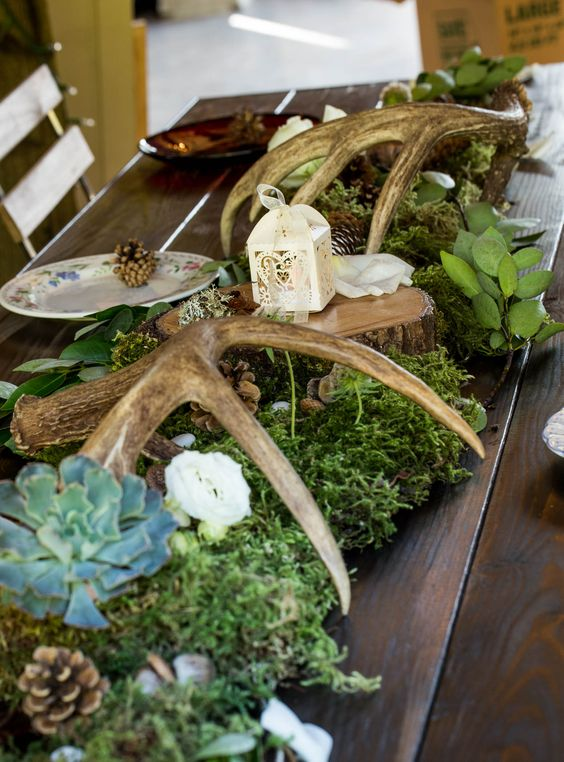 woodland wedding table decor with moss, succulents, pinecones, antlers, greenery and a tiny candle lantern on top