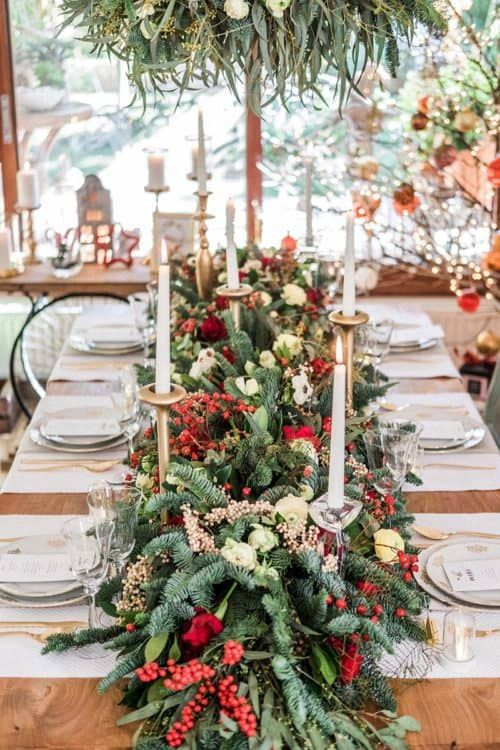 a Christmas wedding tablescape with a greenery and fir runner, with berries and red roses, candles and gold cutlery