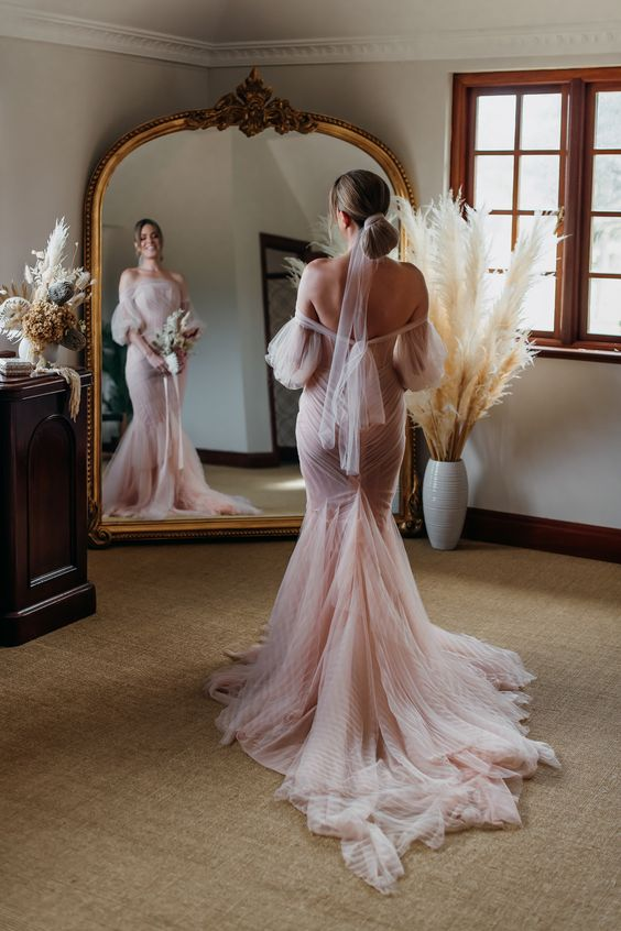a blush off-the-shoulder mermaid wedding dress with puff sleeves and a train plus a blush wrap for the hair