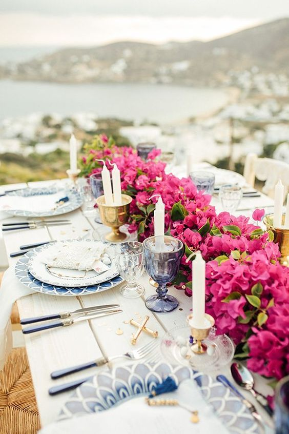 a bold Grecian wedding tablescape with radiant orchid table runners, blue porcelain, candles in gold candleholders