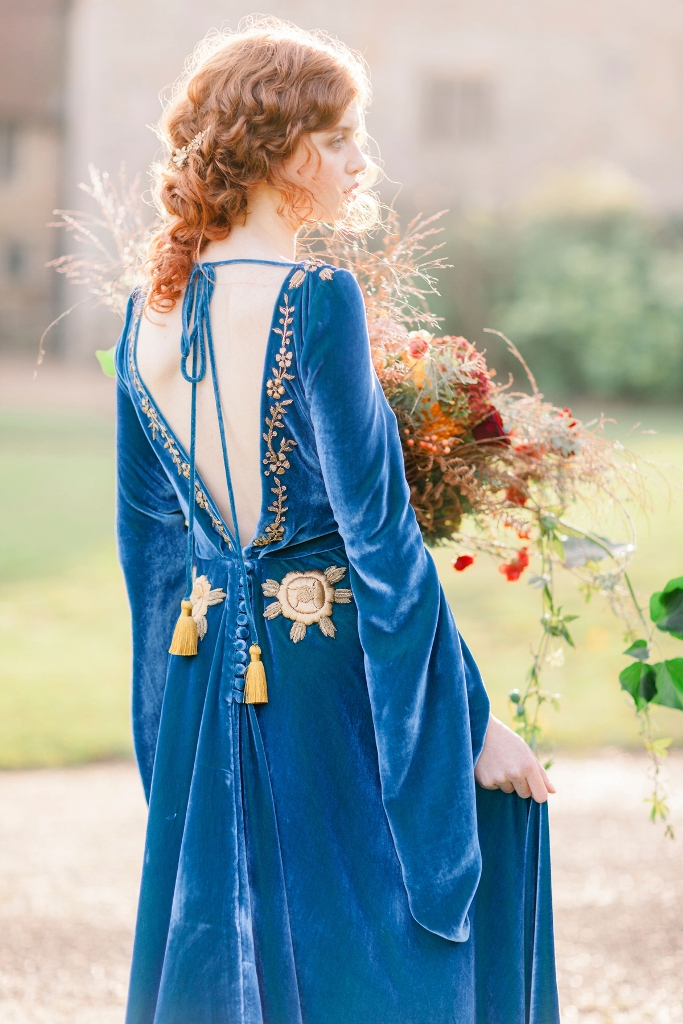 a bold blue velvet wedding dress with an open back, gold embroidery and embellishments, gold tassels for a fall bride