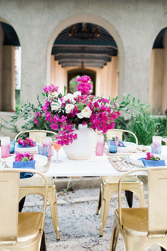 a bold floral wedding centerpiece of white and radiant orchid blooms and greenery, ombre radiant orchid glasses and pink touches