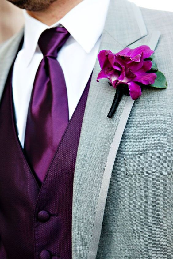 a bold groom's look with a grey suit, a radiant orchid vest, a matching tie and a boutonniere is a statement idea