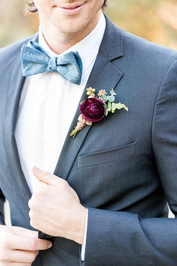 a bold purple bloom, berry and greenery boutonniere is a colorful accent for a winter groom's look done in grey and blue