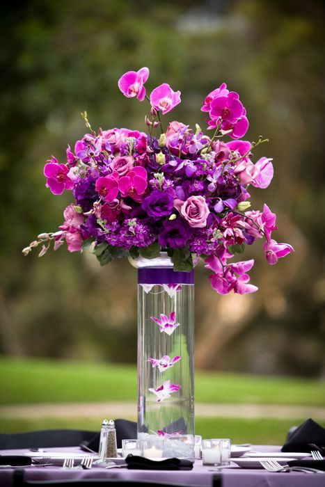 a bold radiant orchid wedding bouquet with purple and pink blooms in a sheer vase is a chic wedding centerpiece